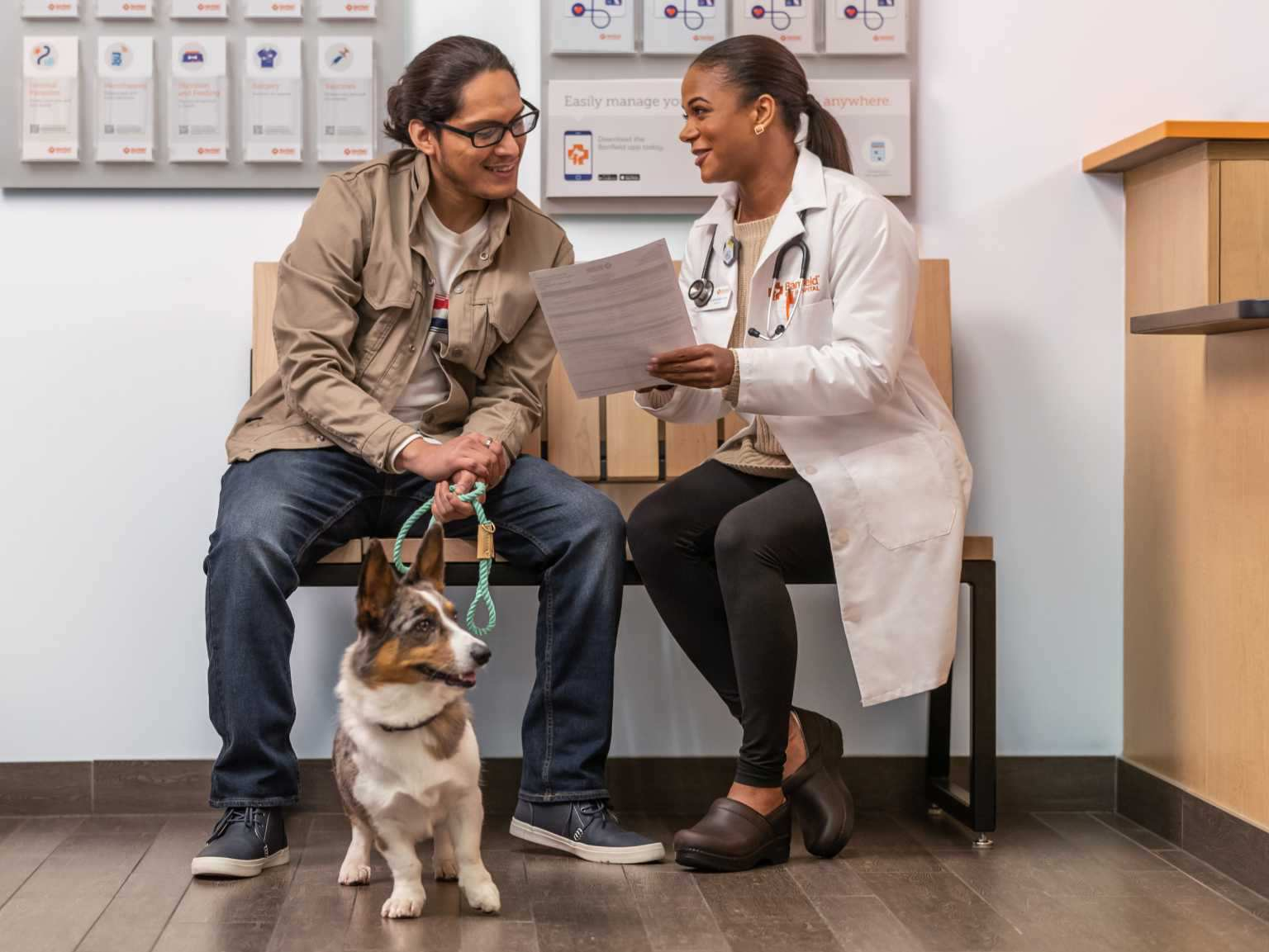 A female veterinarian explaining a medical report to a dog owner, who is holding his dog on a leash at the Banfield Pet Hospital