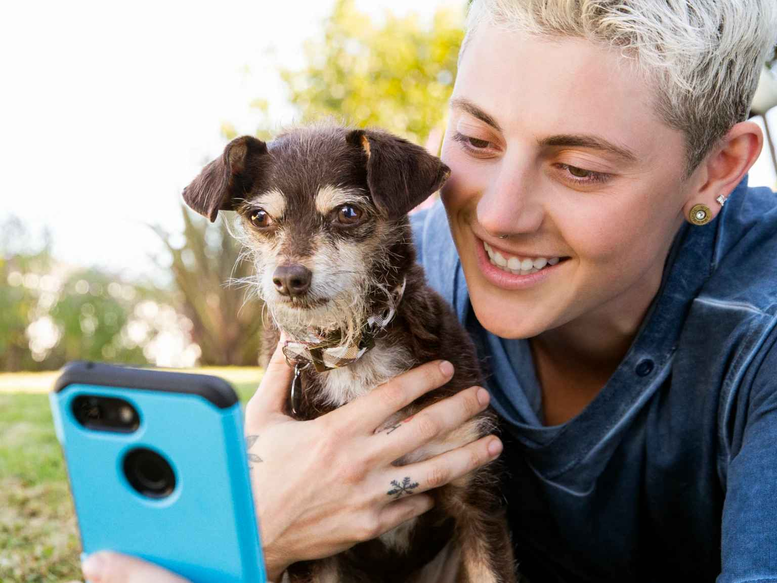 An owner and their puppy using a smart phone.