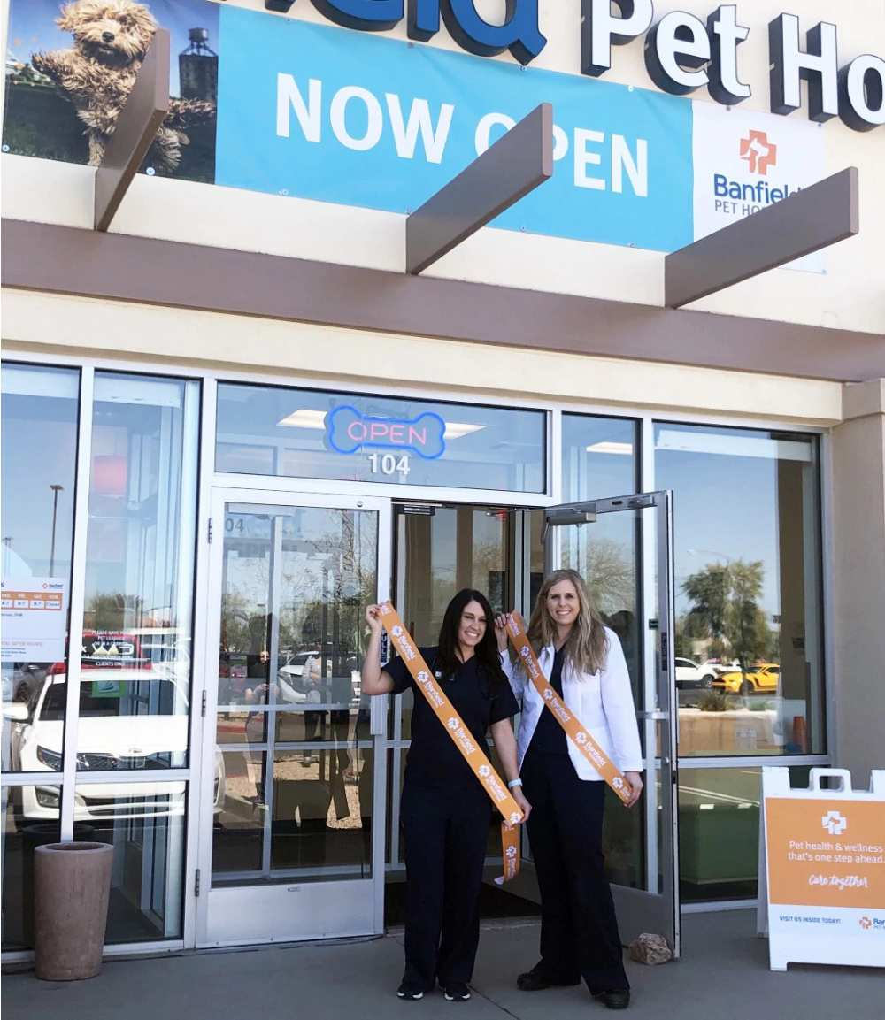 A couple of young female Banfield associates standing at the entrance of the Banfield Pet Hospital