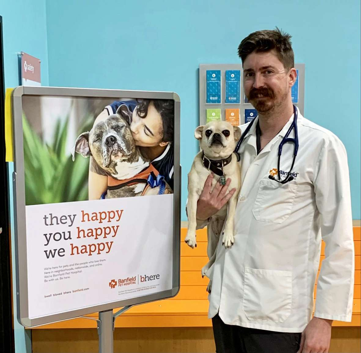 A male veterinarian holding a dog at the Banfield Pet Hospital